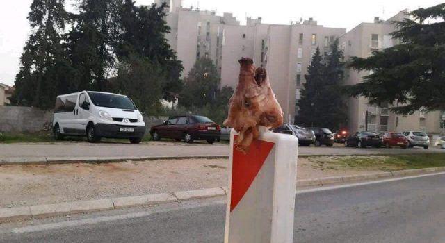 SMIJEŠNO ILI BOLESNO? Glavu pečene svinje nataknuli na prometni znak!